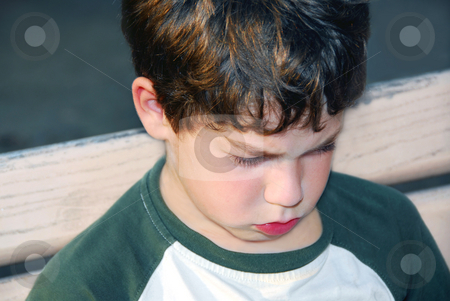 Sad boy stock photo, Portrait of a sad boy sitting on a bench in a park by Elena Elisseeva