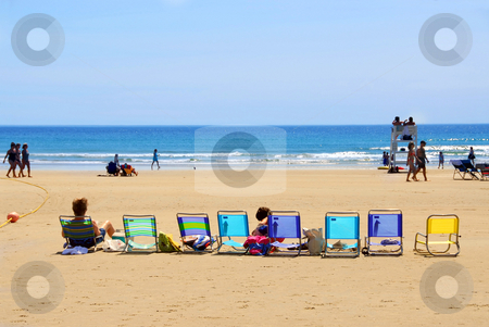 Beach stock photo, A row of colorful folding chairs on a sandy beach by Elena Elisseeva