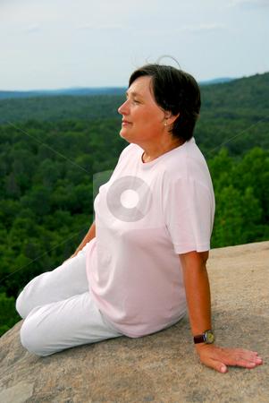 Pondering woman on cliff edge stock photo, Mature woman sitting on cliff edge enjoying scenery by Elena Elisseeva