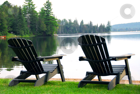 Lake beach chairs stock photo, Two wooden chairs on a lake shore in the evening by Elena Elisseeva