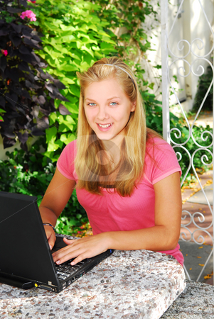 Girl with computer stock photo, Smiling teenage girl typing on a portable computer outside by Elena Elisseeva