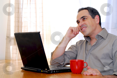 Man with laptop stock photo, Man sitting at a desk and looking into his computer by Elena Elisseeva