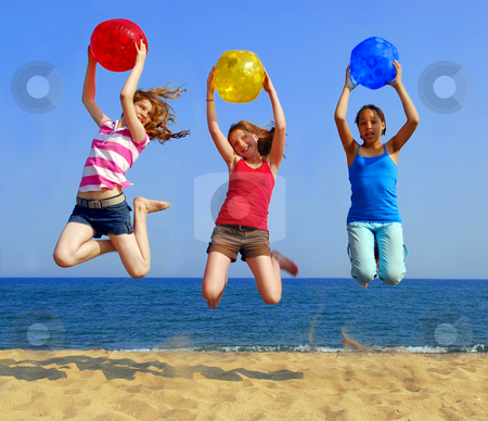 Girls on beach stock photo, Three girls with colorful beach balls jumping on a seashore by Elena Elisseeva