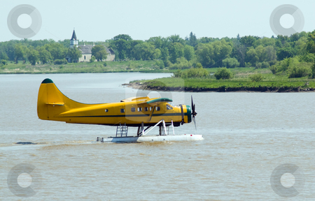Water Plane stock photo, A yellow water planet floating on the river, preparing for take-off by Richard Nelson