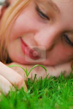 Girl and seedling stock photo, Closeup on a face of a young girl watching a new seedling grow by Elena Elisseeva