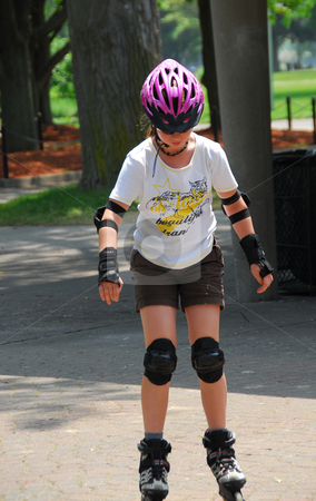 Girl rollerblading stock photo, Young girl rollerblading in a summer park by Elena Elisseeva