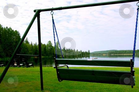 Bench swing stock photo, Bench swings on lake shore by Elena Elisseeva
