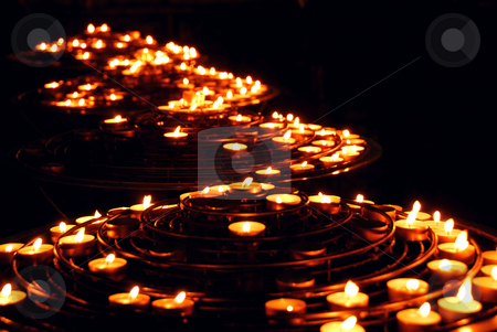 Burning candles stock photo, Rows of burning candles in a cathedral by Elena Elisseeva