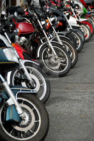 Row of motobikes stock photo, Row of motocycles parked on a street in front a motorcycle store by Elena Elisseeva