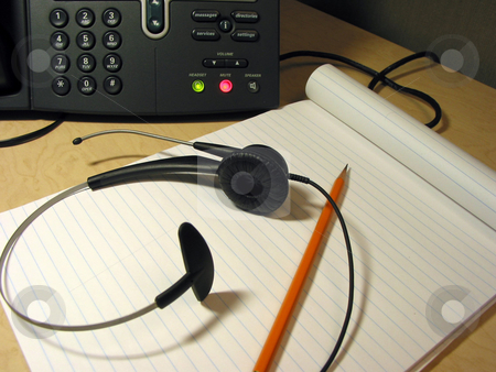 Customer support 7 stock photo, Headset, pencil and notepad on the office desk with IP phone in the background by Elena Elisseeva