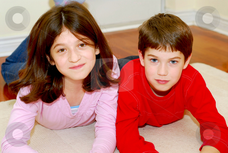 Siblings stock photo, Portrait of brother and sister playing on the floor by Elena Elisseeva