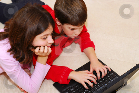 Siblings stock photo, Portrait of brother and sister looking into computer by Elena Elisseeva