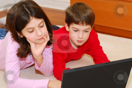 Siblings stock photo, Children lying on the carpet with portable computer by Elena Elisseeva