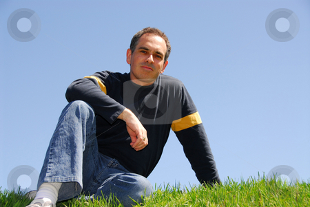 Man sitting on grass stock photo, Man sitting on grass, cloudless sky background by Elena Elisseeva