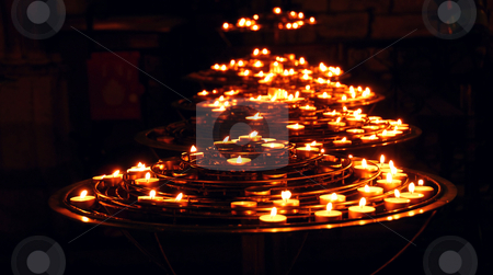 Burning candles stock photo, Rows of burning candles inside a cathedral by Elena Elisseeva