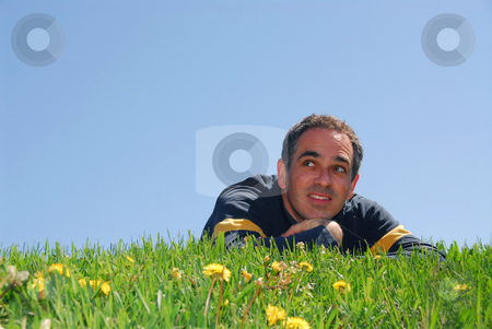 Man on grass stock photo, Man lying on grass, blue sky background by Elena Elisseeva