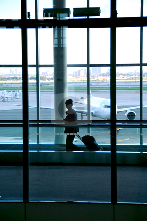 Woman airport stock photo, Woman walking in the airport with luggage by Elena Elisseeva