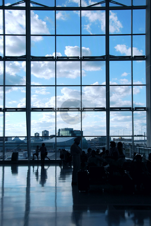 Airport travelers stock photo, People waiting at the international airport terminal, bright blue sky outside by Elena Elisseeva