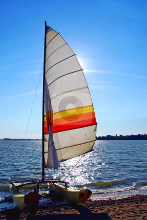 Sailboat backlit stock photo, Catamaran on a beach with backlit sail by Elena Elisseeva