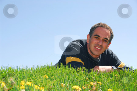 Man on grass stock photo, Smiling man lying on grass on background of blue sky by Elena Elisseeva