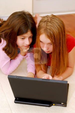 Girls computer stock photo, Portrait of two girls lying on the floor and  looking into computer by Elena Elisseeva