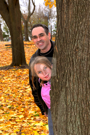 Family park autumn stock photo, Father and daughter peaking from a tree trunk in autumn park by Elena Elisseeva