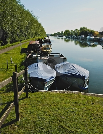 Boats on a canal near bank in sun shine stock photo, Canal boats moored at bank by Stefan Edwards