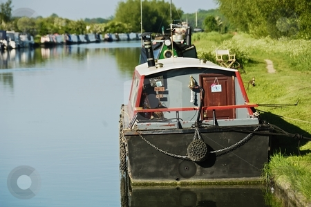 Canal boat at river bank  stock photo, Canal boat moored at grass bank in sunshine by Stefan Edwards