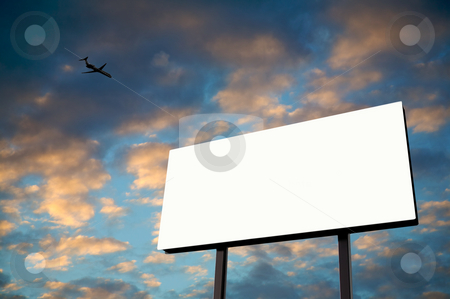 White Billboard with sunset and jet stock photo, Brand new billboard in the setting sun with a jet flying over by Mitch Aunger
