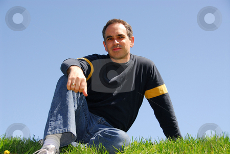Man sky grass stock photo, Man sitting outside on a grass on a background of cloudless blue sky by Elena Elisseeva