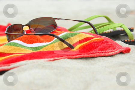 Beach items on sand stock photo, Beach towel, sunglasses and flipflops on white sandy beach by Elena Elisseeva