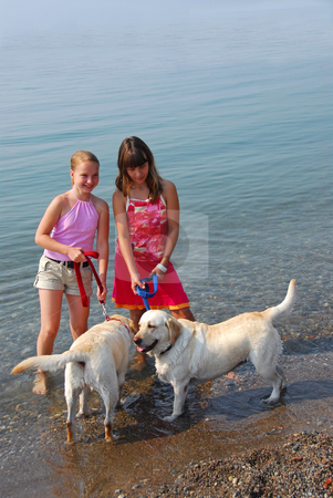 Two girls playing with dogs stock photo, Two girls playing with dogs on a beach by Elena Elisseeva