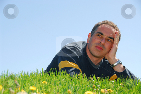 Man grass sky stock photo, Man lying on a grass on a background of blue sky with concerned expression by Elena Elisseeva