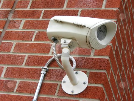 Security camera stock photo, Security camera on a brick wall of a residential building by Elena Elisseeva