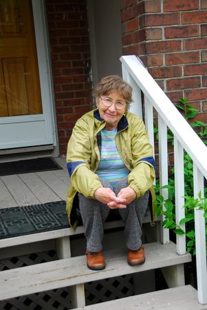 Senior woman smiling stock photo, Senior woman sitting on a porch by Elena Elisseeva