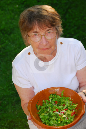 Healthy senior woman stock photo, Happy senior woman with bowl of salad in her hands by Elena Elisseeva