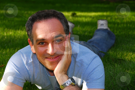 Man relaxing outside stock photo, Man relaxing outside on green grass by Elena Elisseeva