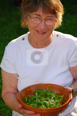 Happy senior woman stock photo, Happy senior woman with bowl of salad in her hands by Elena Elisseeva