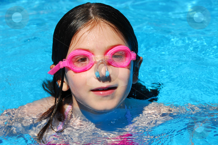 Child swimming pool stock photo, Portrait of a smiling girl in pink goggles in a swimming pool by Elena Elisseeva