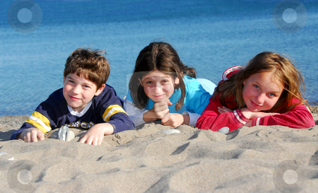 Children on a beach stock photo, Three kinds lying on a beach by Elena Elisseeva