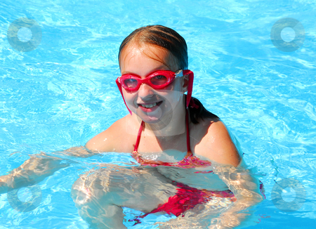 Girl swimming stock photo, Girl in red goggles in swimming pool by Elena Elisseeva