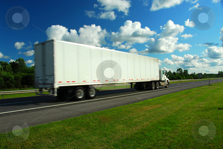 Moving truck stock photo, Fast moving eighteen wheeler on a highway, truck is a bit blurred because of speed by Elena Elisseeva