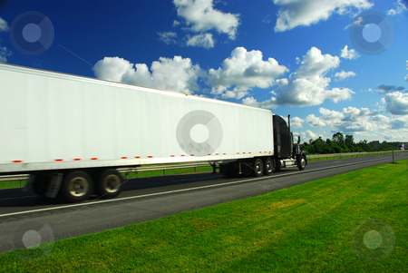 Fast moving truck stock photo, Fast moving truck on highway, blurred because of motion by Elena Elisseeva