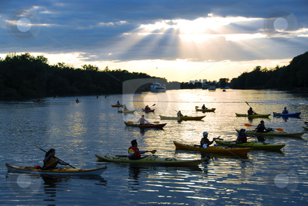 Canoeing stock photo, Group of people canoeing at sunset with sunrays shining through clouds by Elena Elisseeva
