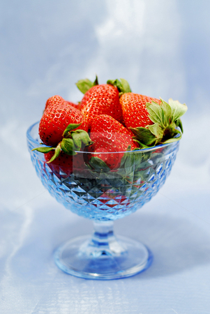 Strawberry still life stock photo, Strawberries in blue glass bowl on blue background by Elena Elisseeva
