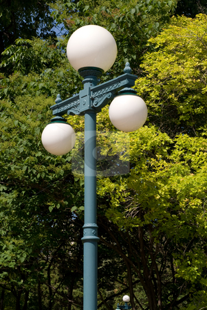 Lamp Post stock photo, A lamp post with three lights on it shot against a green tree by Richard Nelson
