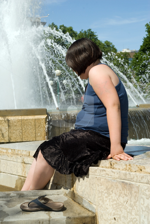 Cooling Off stock photo, A young girl soaking her feet in a large fountain trying to cool off by Richard Nelson