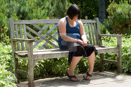 Depression stock photo, A young girl sitting on a park bench outside looking depressed by Richard Nelson