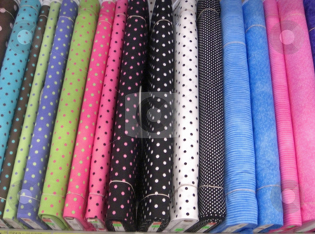 Rolls of fabric stock photo, A variety of colorful fabrics in different textures are neatly displayed on a shelf inside a retail store. by Rebecca Mosoetsa