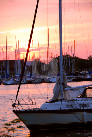 Yacht sunset stock photo, Yacht sailing at beautiful sunset in a harbor by Elena Elisseeva